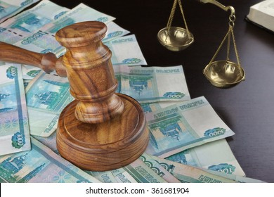 Concept For Corruption, Bankruptcy, Bail, Crime, Bribing, Fraud. Judges Gavel, Scale Of Justice, Old Law Book And Russian Cash On The Rough Black Wooden Textured Table Background.
