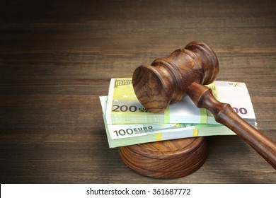 Concept For Corruption, Bankruptcy Court, Bail, Crime, Bribing, Fraud, Auction Bidding. Judges or Auctioneer Gavel And Bundle Of Euro Cash On The Rough Wooden Textured Table Background. Top View