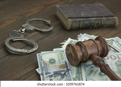 Concept For Corruption, Justice, Law, Bankruptcy Court, Bail, Crime, Bribing, Fraud. Judges Gavel, Soundboard, Real Handcuffs And  Dollar Cash On The Rough Wooden Textured Table Background.