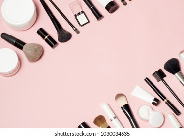 Concept of a cosmetic tubes and cream containers top view on pink background. Lipstick, eyeliner, brush, parfume etc. Place for your inscription in the center