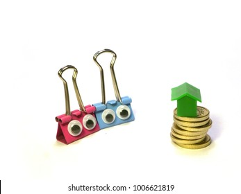 Concept of couple with dream of home ownership but lacking financial resources to get on property ladder illustrated with cute pink and blue bulldog clip figures, pile of coins, and house