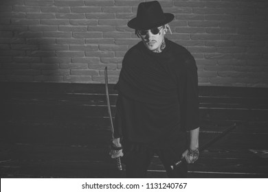concept of courage. Honor and dignity. Warrior in black sunglasses, hat and clothes, top view. Samurai, buddhist concept. Man with swords standing on wooden floor. Harakiri, suicide ritual.