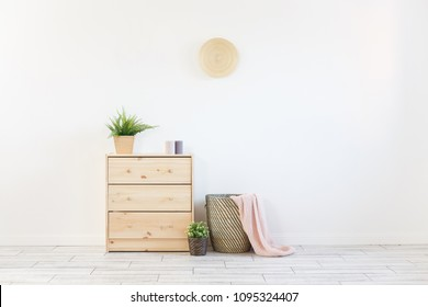 Concept of a cozy interior and housewarming - small wooden chest with accessories and laundry basket on white wall background. Copyspace