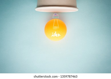 Concept of creative idea, inspiration, innovation and bulb light with ping pong ball and paper cup on blue background with empty space for text