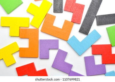 Concept of creative, logical thinking. Different colorful shapes wooden blocks on white background, flat lay, copy space. Geometric shapes in different colors, top view. Selective focus.