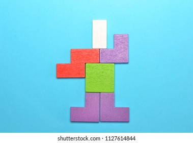 Concept of creative, logical thinking. Different colorful shapes wooden blocks on blue background, flat lay, copy space, Geometric shapes in different colors, top view. Selective focus.