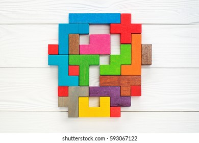 Concept of creative, logical thinking. Different colorful shapes wooden blocks on white wooden background, flat lay, copy space. Abstract question mark made of wooden blocks, top view.