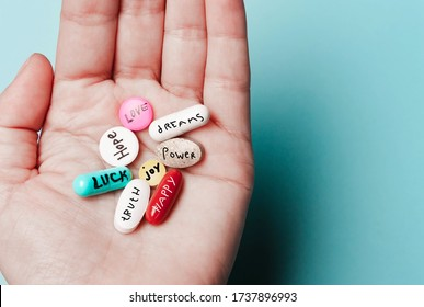 The concept of creative pills, a placebo in the hand, with joy, love, happiness, truth, power, dream on a blue background
