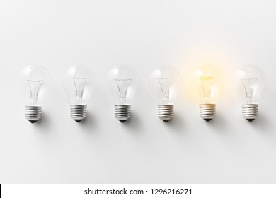 Concept for creativity, innovation and solution. Illuminated light bulb in row of dim ones on white background