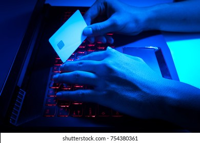 The concept of credit card theft. Hackers with credit cards on laptops use these data for unauthorized shopping. Unauthorized payments from credit card owners. Side view