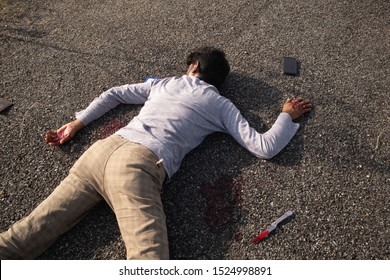 Concept of Crime or murder scene, Closeup of victim dead body murdered with knife lying on Roadside.