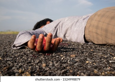 Concept of Crime scene ,Selective focus to victim hand with blood of a dead body lying on Road