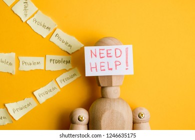 """Concept cry for help in solving problems. Torn stickers with the word """"problem"""" with a piece of paper with the inscription """"need help"""" on wooden mannequin."""