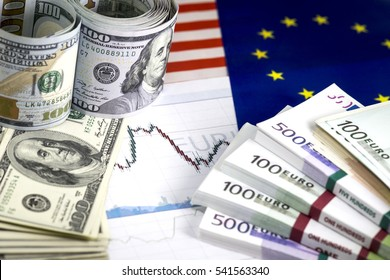 Concept of currency exchange trading. . Roll of Hundred us dollar bills . Piles of euro bills. Currency us euro exchange chart. 200 euro bills, 100 euro bills. US ans European community flags.