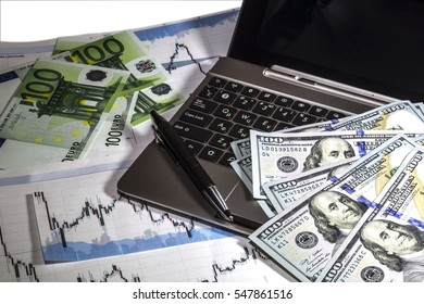 Concept of currency trading. .Hundred us dollar bills lying on tablet. Currency us dollar euro exchange chart under the bills. Hundred Euro bills lying near tablet. Pen on the keyboard.