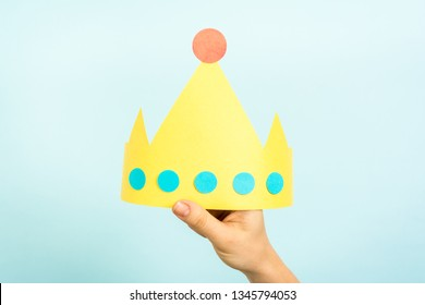 Concept of customer experience, best excellent services rating, satisfaction business, leadership and gender equality. Hand of woman holding a yellow crown with blank space for text.