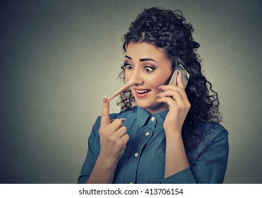 Concept of customer support representative liar with long nose. Portrait young woman talking on mobile phone telling lies isolated on gray wall background. Human face expressions