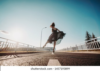 Concept dancepics outdoors dance and female beauty. Beautiful brunette woman in black dress and pointe dancing over city background jumps on the road from the back