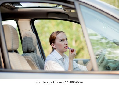 Concept of danger driving. Young woman driver red haired teenage girl painting her lips doing applying make up while driving the car.
