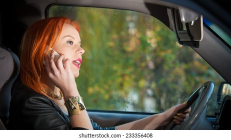 Concept of danger driving. Young woman driver redhaired girl talking on mobile phone smartphone while driving the car.