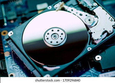 The concept of data, hardware, and information technology, the image of inside of hard disk drive on the technician's desk and a computer motherboard, toned