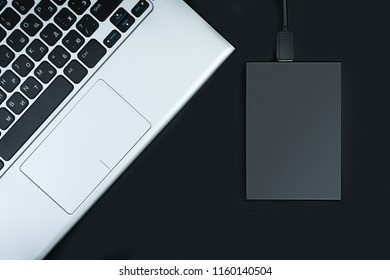 The concept of data storage. A portable hdd connected to a laptop with usb flash drive on a black table, flat lay.