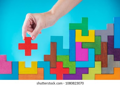 Concept of decision making process, logical thinking. Logical tasks. Conundrum, find the missing piece of the proposed. Hand holding puzzle element. Background with colorful shapes wooden blocks