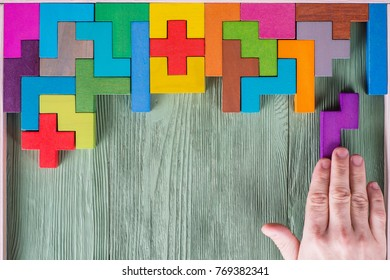 Concept of decision making process, logical thinking. Find the missing piece of the proposed. Hand holding puzzle element. Background with colorful shapes wooden blocks
