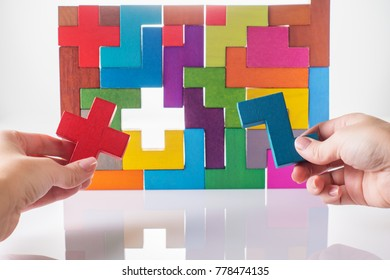 Concept of decision making process, logical thinking. Logical tasks. Conundrum, find the missing piece of the proposed. Hand holding wooden puzzle element. Hand sets the last element of the puzzle