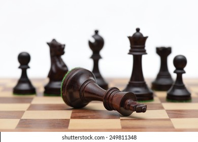 Concept of defeat (fallen king, camera focus on black king chess piece, background blurred)