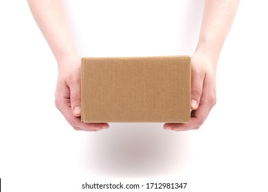 Concept of delivery, package, storage, transfer of the package. Women's hands hold a cardboard box on a white background. Close-up. Mock-up.