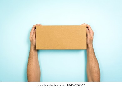 Concept of delivery and storage. Man showing a cardboard box with empty space for text. Only hands holding a closed box on blue background.