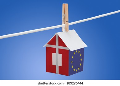 concept - Denmark and EU flag painted on a paper house hanging on a rope