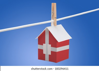 concept - Denmark flag painted on a paper house hanging on a rope