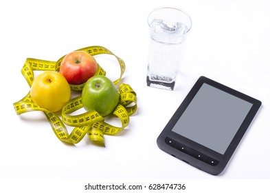 Concept of diet, fresh apples and a glass of water on a light background. A healthy diet, apples, a measuring tape and a tablet on the table, space for your text.