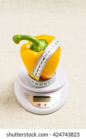 Concept of diet, health. Yellow sweet bell pepper with a meter on the white balance. Selective focus.