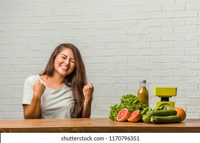 Concept of diet. Portrait of a healthy young latin woman very happy and excited, raising arms, celebrating a victory or success, winning the lottery