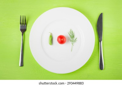 the concept of dietary restrictions, healthy lifestyle, diet,  weight loss, anti-obesity, healthy diet. Small tomato, green peas, a sprig of dill on a plate, knife, fork on the table, top view
