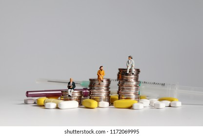 A concept of the difference in health care costs. Miniature people sitting on coins with pills and syringes.