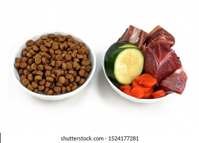 Concept for different dog feeding methods with bowl with dry food kibbles and bowl with chunk of raw meat and vegetables next to each other isolated on white background