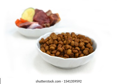 Concept for different dog feeding methods with bowl with dry food kibbles in front and blurry bowl with chunk of raw meat and vegetables in back isolated on white background