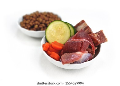 Concept for different dog feeding methods with bowl with bowl with chunk of raw meat and vegetables in front and blurry dry food kibbles in back isolated on white background