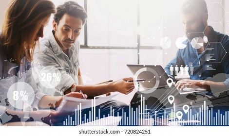 Concept of digital diagram,graph interfaces,virtual screen,connections icon on blurred background.Group of three young coworkers working together at modern coworking studio