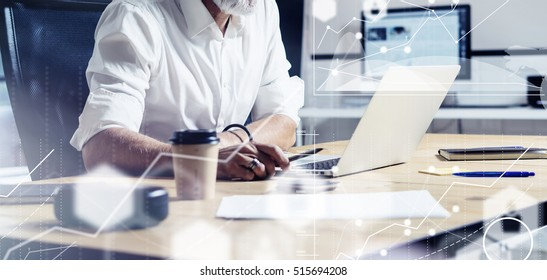 Concept of digital screen with virtual icon,diagram, graph and interfaces.Adult professional businessman wearing a classic glasses working at the wood table in modern coworking studio.Horizontal wide