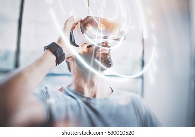 Concept of digital screen,connection and interfaces.Attractive bearded man enjoyingvirtual reality glasses in modern loft studio.Smartphone using with VR goggles headset.Flare effect,blurred