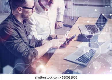 Concept of digital screen,virtual connection icon,diagram, graph interfaces.Adult businessman working together with young partner at the wooden table in modern office.Flares,blurred
