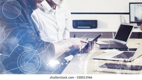 Concept of digital screen,virtual connection icon,diagram,graph interfaces.Bearded young man holding mobile phone and touching display.Adult businessman working together with partner.Film effect,wide.