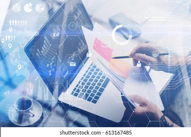 Concept of digital screen,virtual connection icon,diagram,graph interface.Adult tattooed coworker working with laptop at workplace.Businessman analyze documents on hands.Visual effect