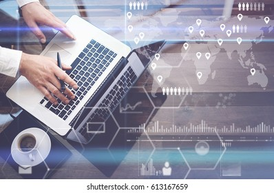 Concept of digital screen,virtual connection icon,diagram,graph interfaces.Businessman working with laptop at office.Modern notebook,cup of black coffee on wooden table.Reflections on glass surface