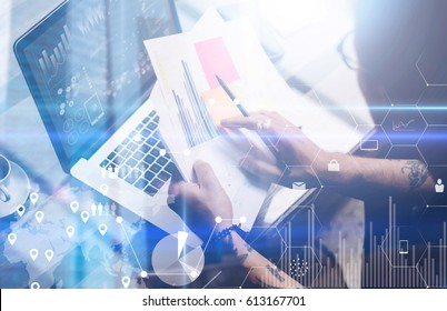 Concept of digital screen,virtual connection icon,diagram,graph interface.Adult tattooed coworker working with laptop at workplace.Businessman analyze documents on hands.Double exposure,visual effect